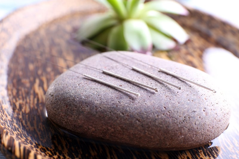 Acupuncture needles on stone